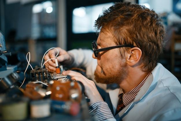 Scienziato che prototipa dispositivo elettrico in laboratorio