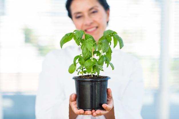 Scienziato che tiene pianta di basilico
