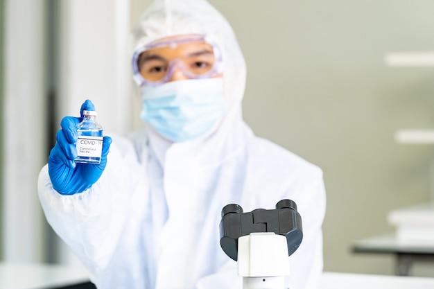 Scienziato con tuta in dpi detiene il vaccino covid-19