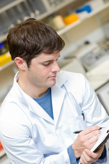 Scienziato concentrato che scrive su una lavagna per appunti