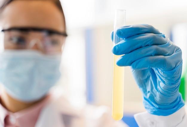 Scienziato femminile sfocato che tiene sostanza di laboratorio