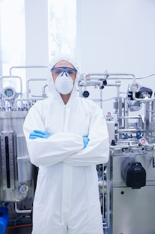 Scienziato in tuta protettiva in piedi con le braccia incrociate