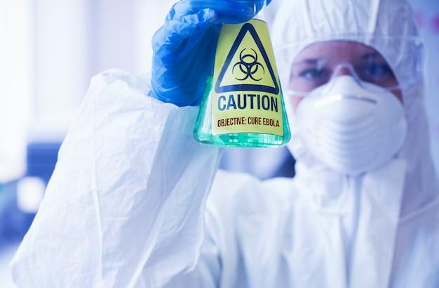 Scienziato in tuta protettiva tenendo becher