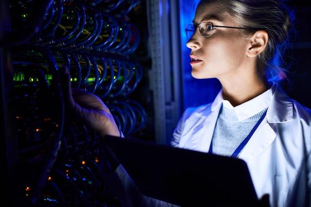 Scienziato informatico femminile che controlla server