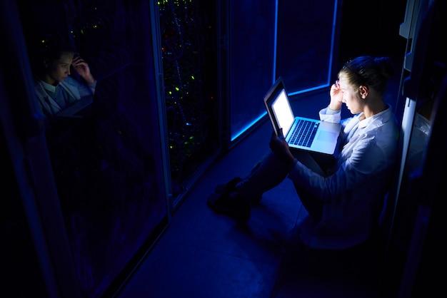 Scienziato informatico femminile che lavora di notte