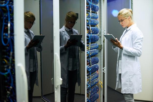 Scienziato informatico femminile che lavora nel centro dati