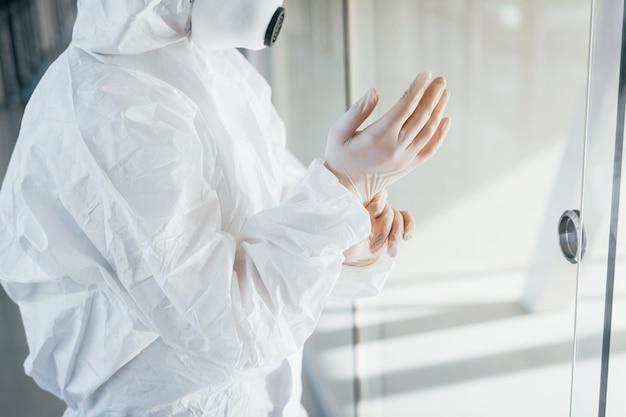 Scienziato medico femminile in camice da laboratorio, occhiali difensivi e maschera in piedi all'interno e indossando guanti