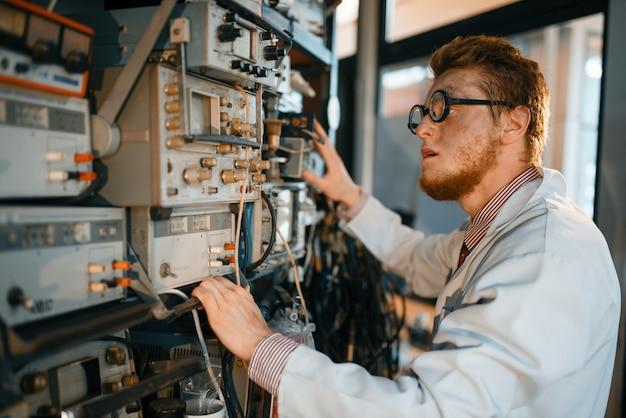 Scienziato pazzo in bicchieri regola il dispositivo elettrico in laboratorio.