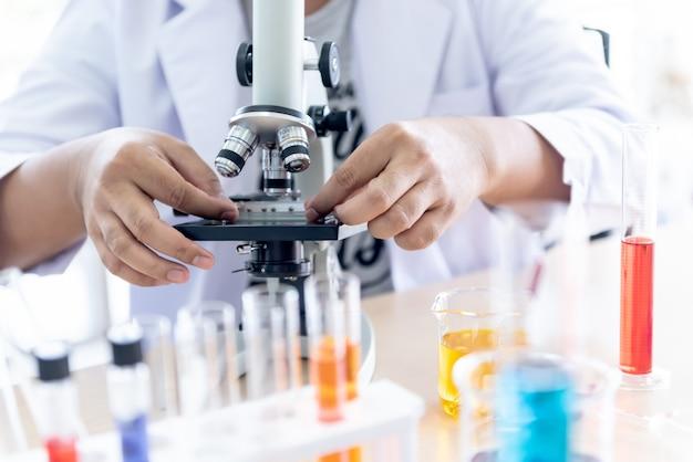 Scienziato utilizzo di un microscopio per l'ispezione del prodotto al fine di ottenere la qualità richiesta