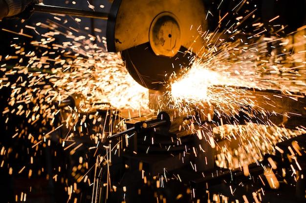 Scintille di metallo fuso volano sotto lo strumento della saldatrice