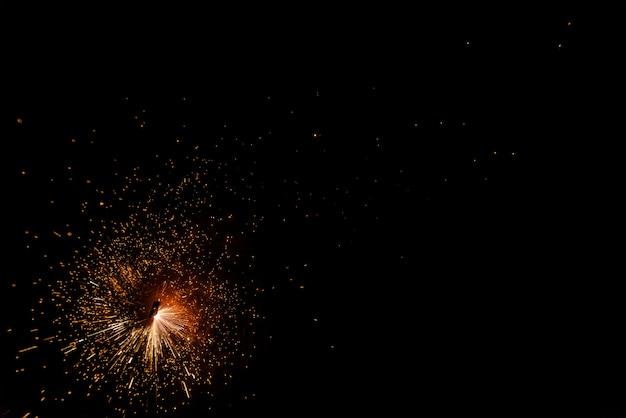 Scintille di un fuoco durante la notte, sfondo nero.