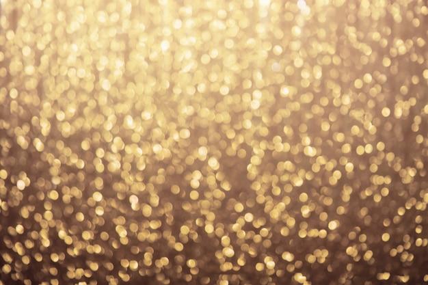 Scintillii glitter dorati sfocati, sfondo festivo