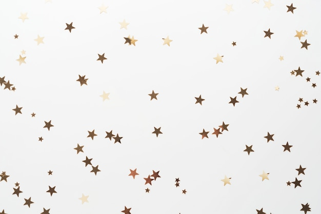 Scintillio dorato, stelle di coriandoli isolate su bianco. sfondo di natale, festa o birthdau.