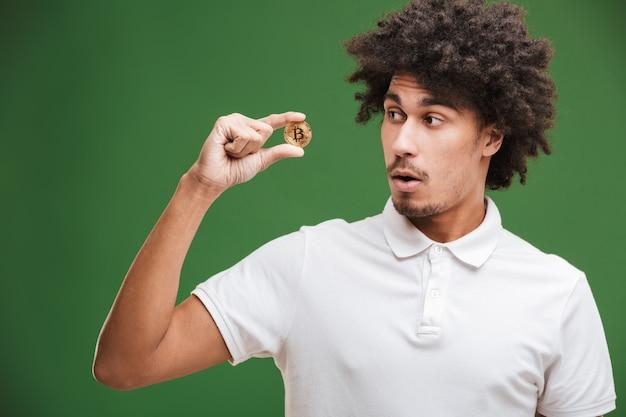 Scioccato giovane africano uomo riccio tenendo bitcoin.