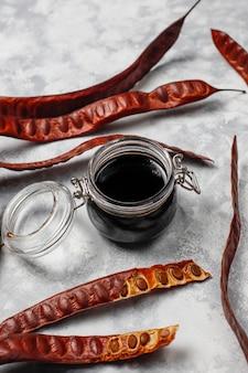 Sciroppo di carruba in barattolo di vetro con baccelli e semi di carruba su luce
