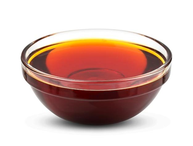 Sciroppo dorato isolato su bianco, miele in ciotola