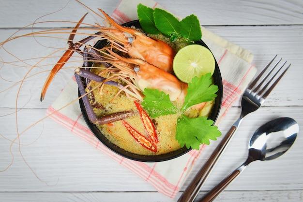 Scodella di gamberi speziati con frutti di mare e tavolo da pranzo con zuppa di gamberi, tom yum kung