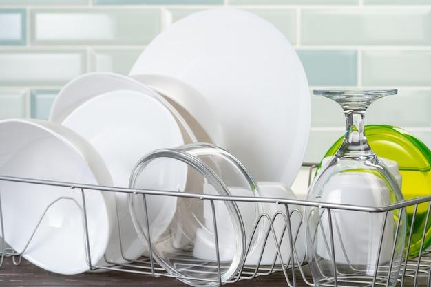 Scolapiatti con piatti asciutti e puliti sul bancone della cucina