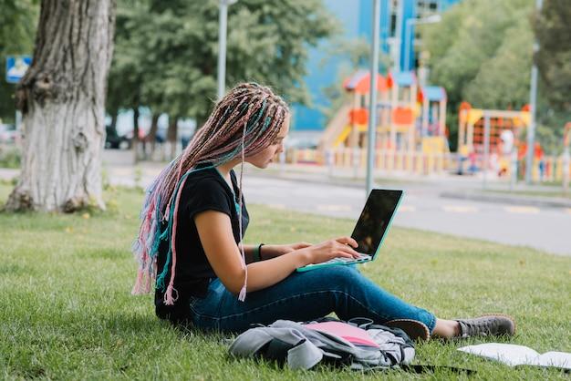 Scolara alla moda nel parco con il computer portatile