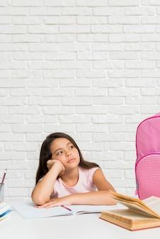 Scolara annoiata ispanica seduto alla scrivania