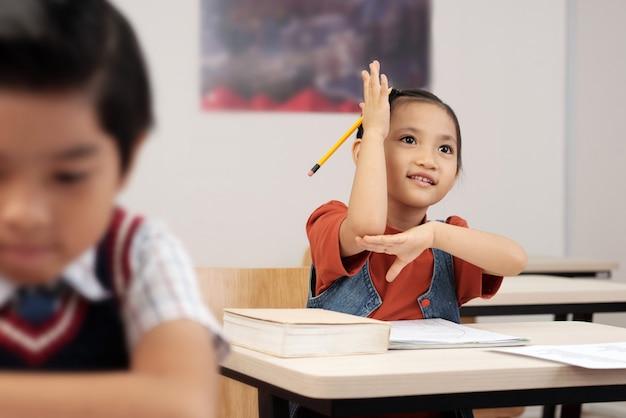 Scolara asiatica che si siede allo scrittorio in aula e che alza la sua mano per rispondere