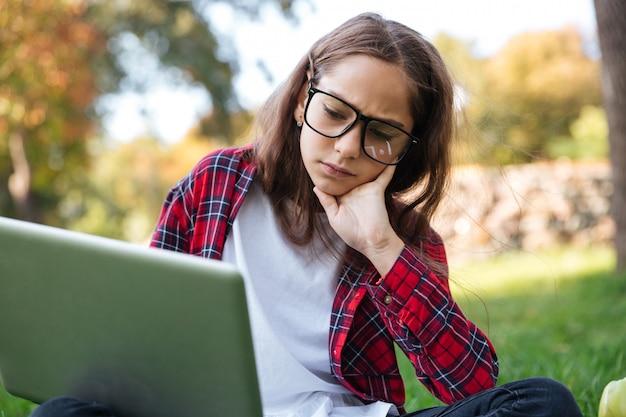 Scolara castana stanca in occhiali che si siedono sull'erba all'aperto