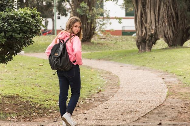 Scolara che cammina nel parco