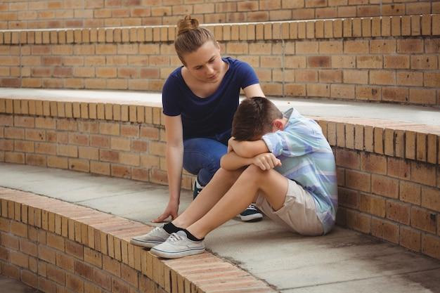 Scolara che consola il suo amico triste sui gradini nel campus