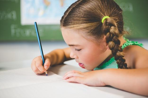 Scolara che fa i compiti in aula