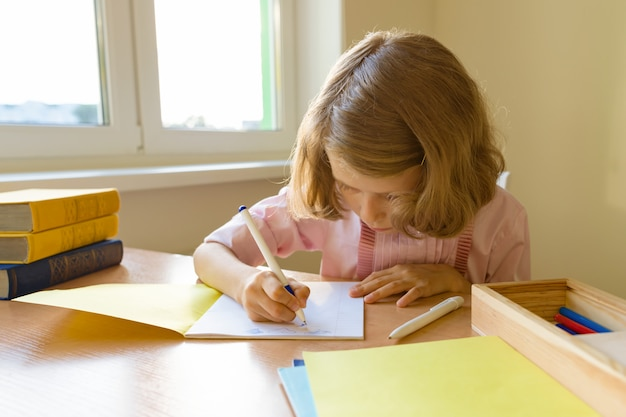 Scolara che si siede alla tavola con i libri e che scrive in taccuino