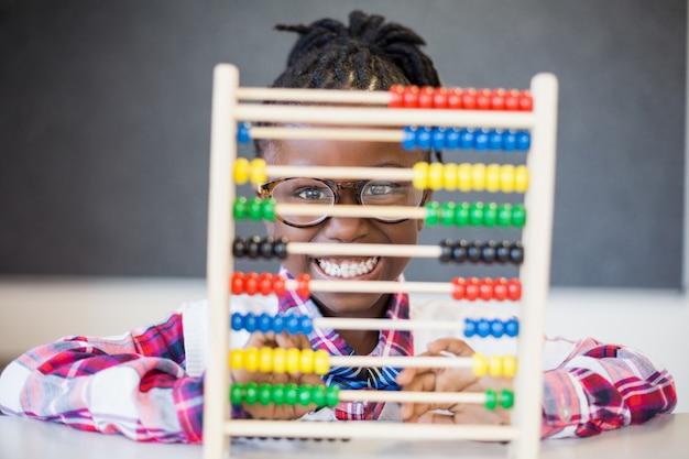 Scolara che usando un abbaco di matematica a scuola