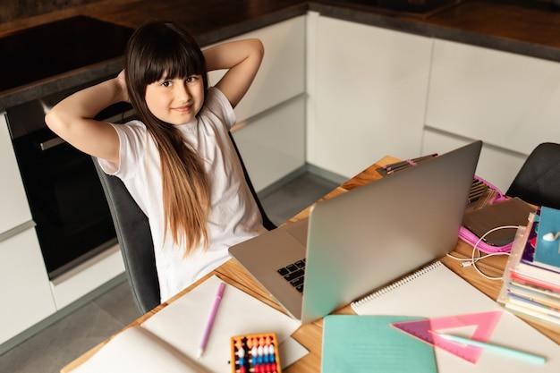 Scolara con un computer portatile a casa. apprendimento online. formazione a distanza durante la quarantena