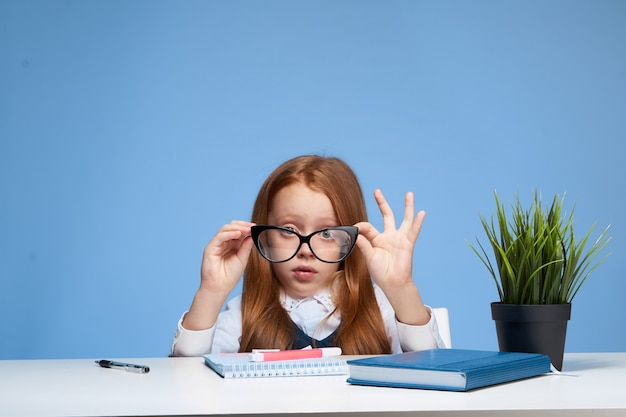 Scolara del bambino della bambina che fa i compiti che si siedono ad una tavola