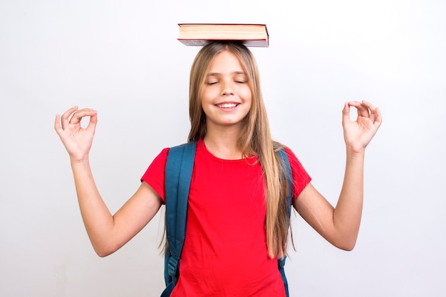 Scolara diligente che porta libro sulla testa