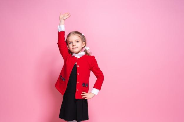 Scolara divertente in uniforme alzando la mano