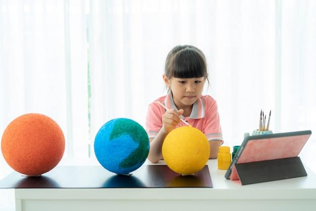 Scolara elementare asiatica che dipinge la luna nella classe di scienza
