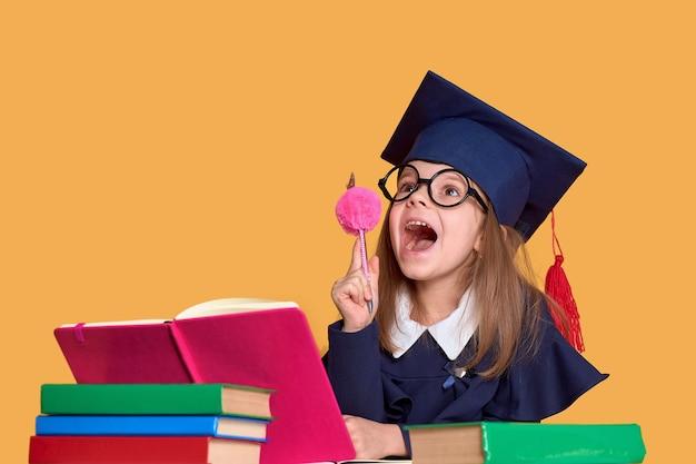 Scolara emozionante in attrezzatura di graduazione che studia con i libri di testo