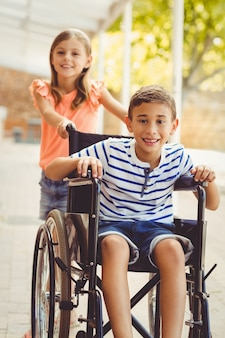 Scolara felice che spinge un ragazzo sulla sedia a rotelle