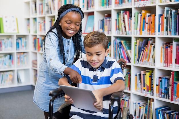 Scolara felice che sta con lo scolaro sulla sedia a rotelle facendo uso della compressa digitale