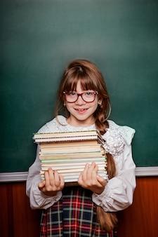 Scolara in uniforme scolastica con una pila di libri, contro lo sfondo di un consiglio scolastico