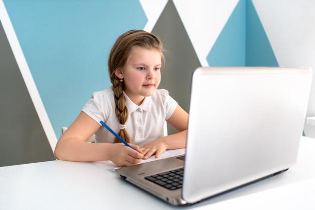 Scolara online di istruzione a distanza di apprendimento che studia a casa con il computer portatile digitale