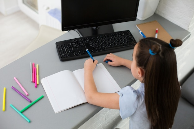 Scolara piuttosto elegante che studia i compiti di matematica durante la sua lezione online a casa, distanza sociale durante la quarantena, auto-isolamento, concetto di istruzione online, scuola a casa