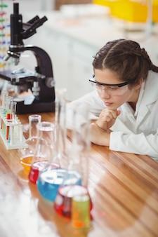 Scolara premurosa che si appoggia sul tavolo in laboratorio