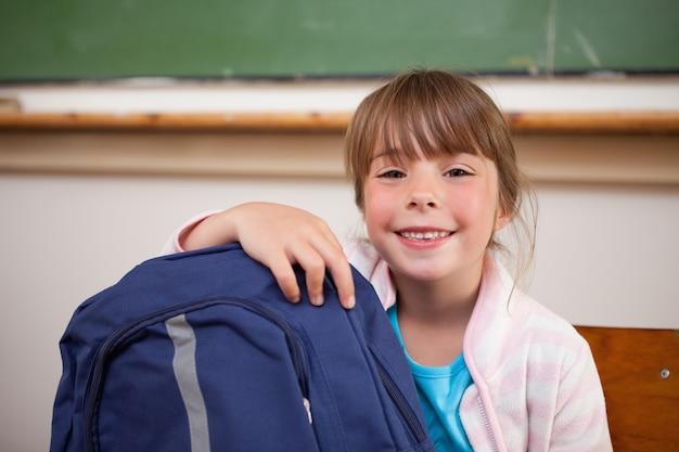 Scolara sorridente che posa con una borsa