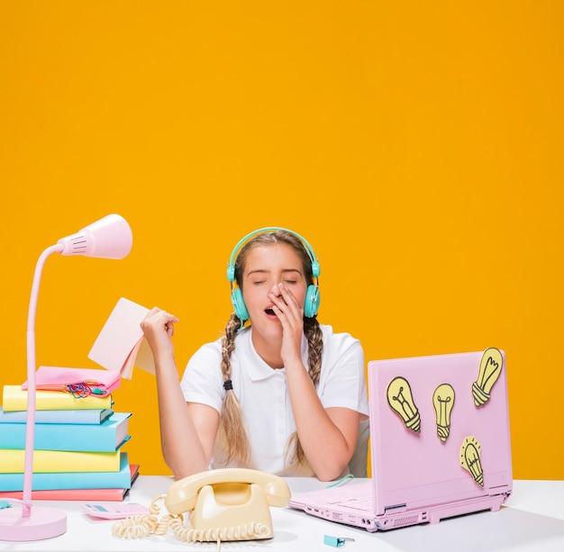 Scolara sulla scrivania con il computer portatile in stile memphis