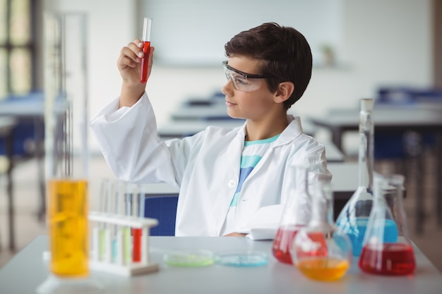 Scolaro attento che fa un esperimento chimico in laboratorio