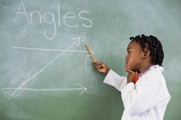 Scolaro che fa matematica sulla lavagna in aula