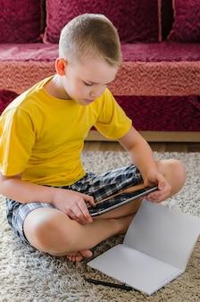 Scolaro che studia a casa con la compressa digitale a disposizione e che fa i compiti della scuola