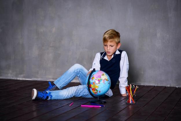 Scolaro con i colori e il globo terrestre. concetto di scuola