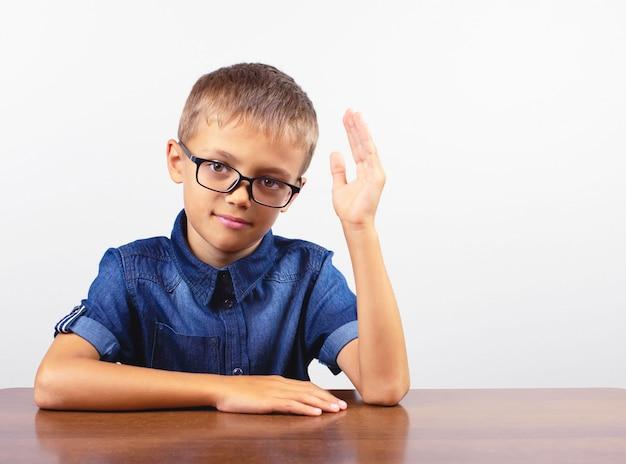 Scolaro dell'insegna in una camicia blu che si siede al tavolo. ragazzo con gli occhiali, concetto di nuovo a scuola